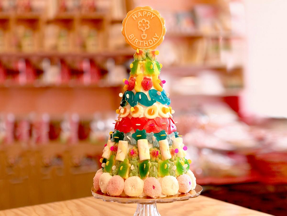 Pièce-montée de bonbons avec une grosse sucette Happy Birthday au-dessus
